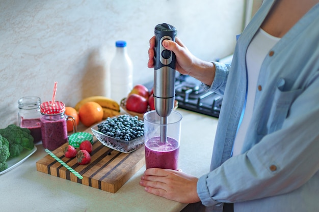 Woman cooking fresh blueberry smoothie using hand blender at kitchen at home. healthy eating