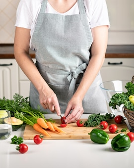 Woman cooking in the kitchen. fresh healthy vegetables on a cutting board