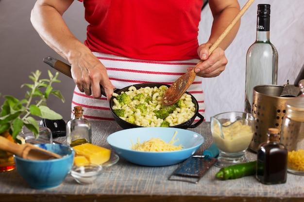 女性が自宅のキッチンでホワイトクリームソースのパスタを調理