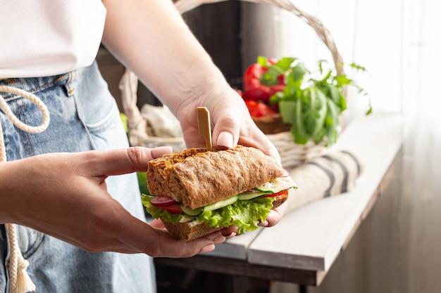 夏のピクニックのためのサンドイッチを調理する女性