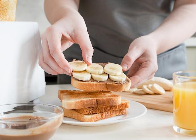 Женщина готовит сладкий тост с арахисовым маслом и бананом. европейский завтрак с тостами и соком.