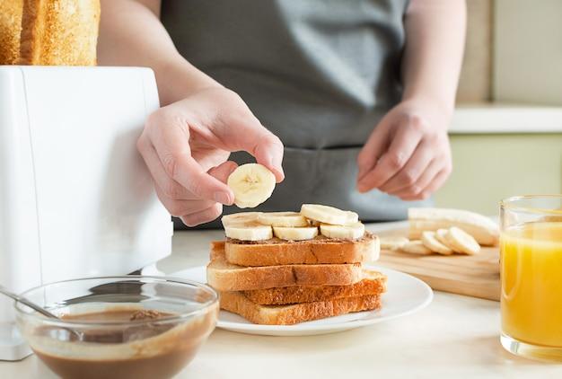 땅콩 버터와 바나나와 함께 달콤한 토스트를 요리하는 여자. 토스트와 주스가 포함 된 유럽식 조식.