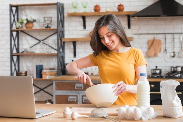 乳製品を使用して調理する女性