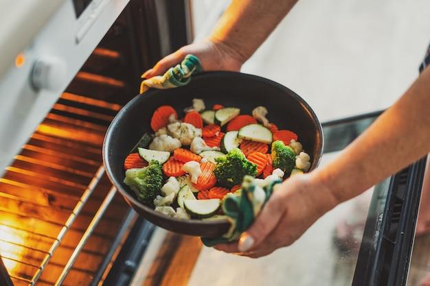 オーブンに野菜と鍋を入れて野菜を調理する女性。家庭料理のコンセプト。
