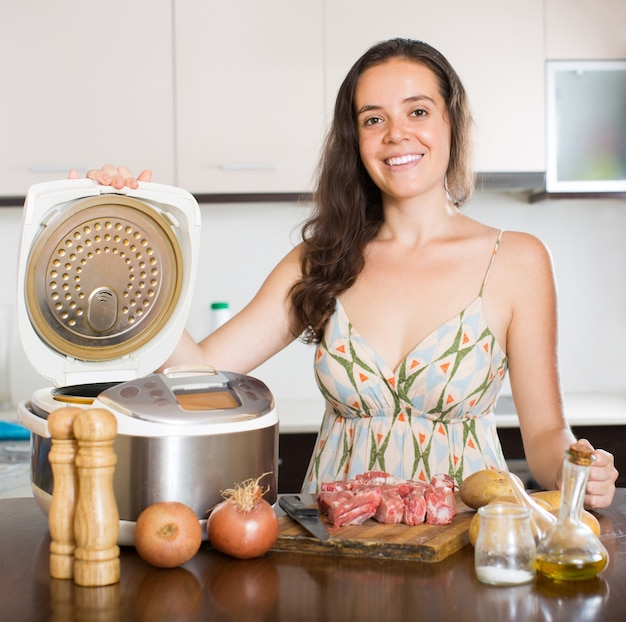 Woman cooking with electric multicooker