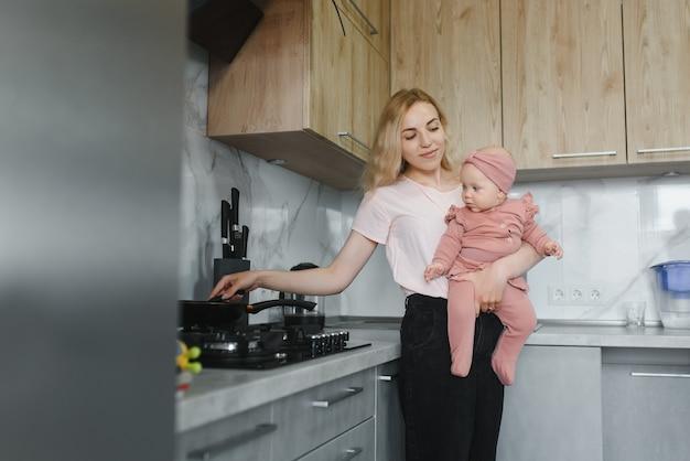 Женщина готовит с маленькой дочерью в руках