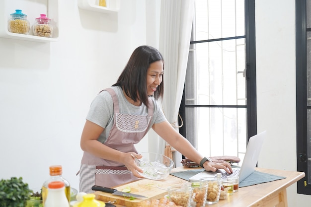 Woman cooking with receipt on laptop in the kitchen