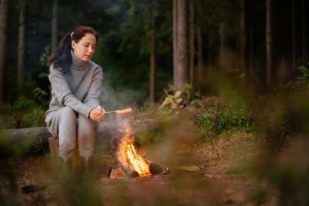 女性はキャンプファイヤーの木の棒でソーセージを調理しますハイキングとレクリエーションの概念
