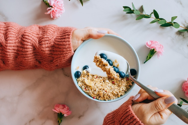 Woman in coral woolen sweater eating breakfast bowl with muesli and yogurt, berries and hazelnuts