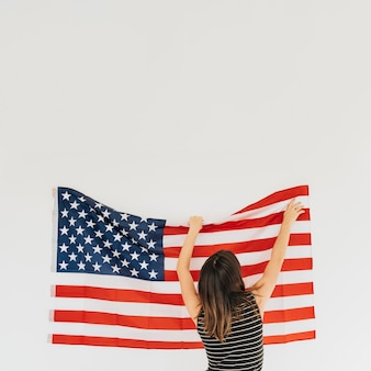 Woman correcting flag of america on wall
