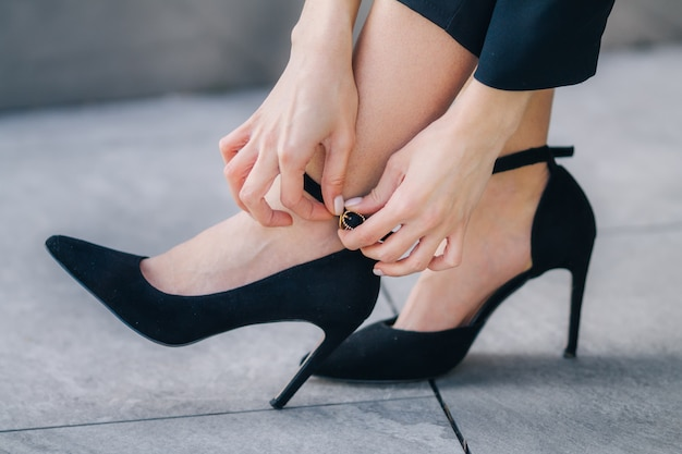 The woman corrects black high heel shoes