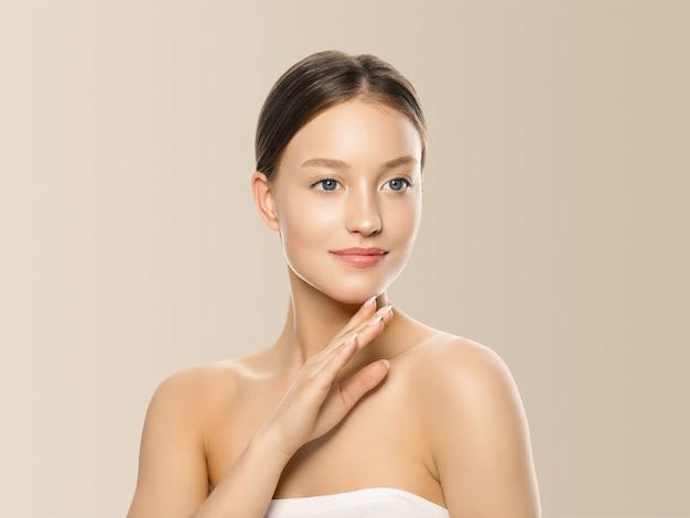 ベージュ色の背景の上の手健康ケア肌の髪と女性の化粧品のクローズアップ美容肖像画