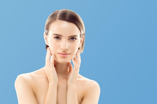 手で女性の化粧品のクローズアップの美しさの肖像画、青い色の背景の上の健康なケア肌の髪