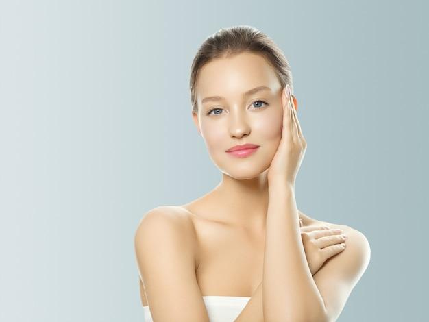 手で女性の化粧品のクローズアップの美しさの肖像画、灰色の背景の上の健康なケア肌の髪