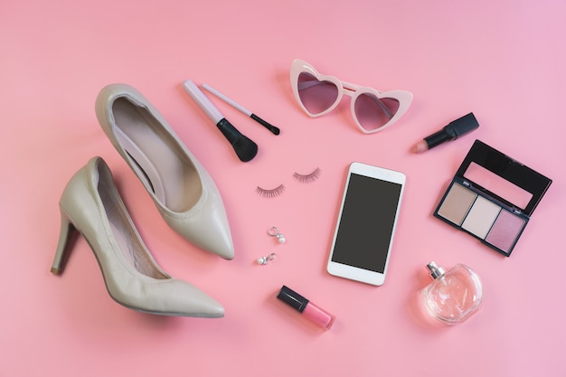 Woman cosmetics, accessories and smartphone on pink