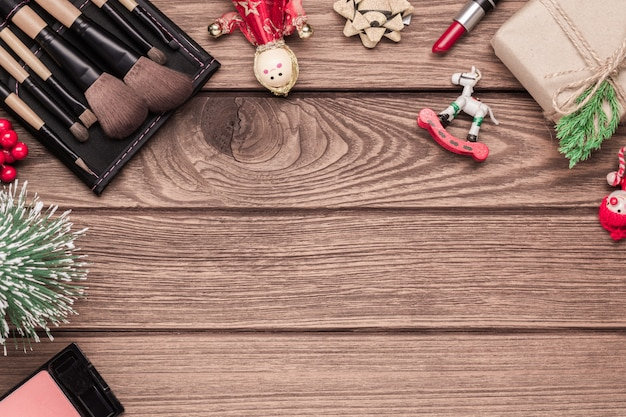 Woman cosmetics, makeup brushes, lipstick and christmas ornaments on wood