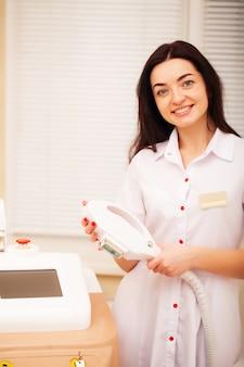 Woman cosmetologist in white coat in beauty studio