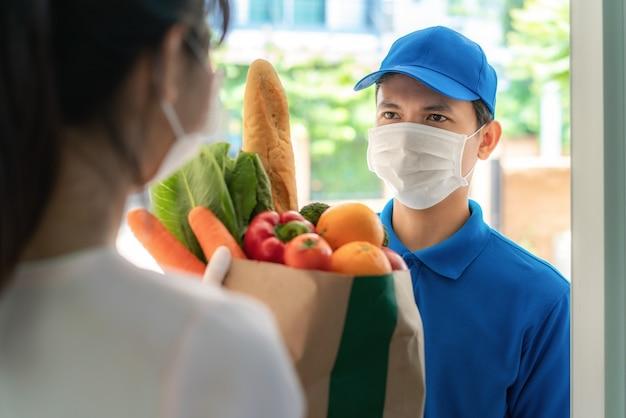 얼굴 마스크와 장갑을 착용하는 여성 costumer는 음식의 식료품 상자를받습니다.