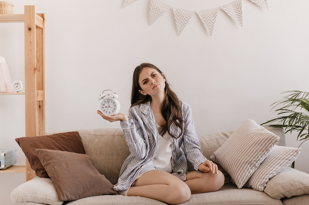 Woman in cotton pajamas is sitting on soft sofa and holding alarm clock