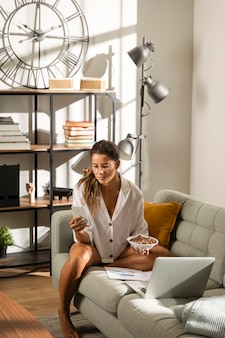 Woman on couch eating in front of laptop