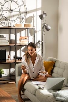 Donna sul divano a mangiare davanti al computer portatile