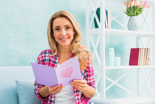 Woman on couch holding greeting card with mom inscription