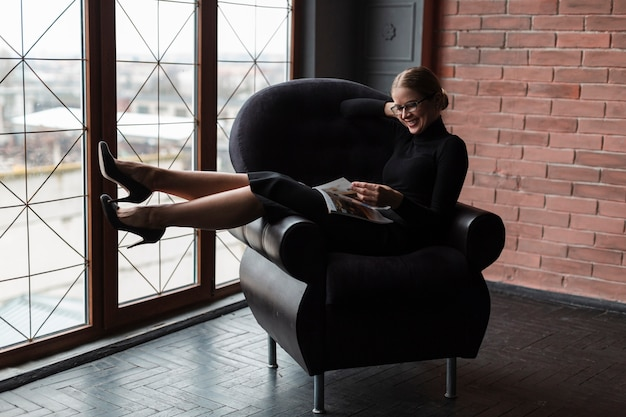 Woman on couch reading magazine