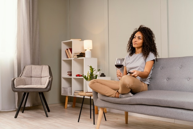 Woman on couch watching tv and drinking wine
