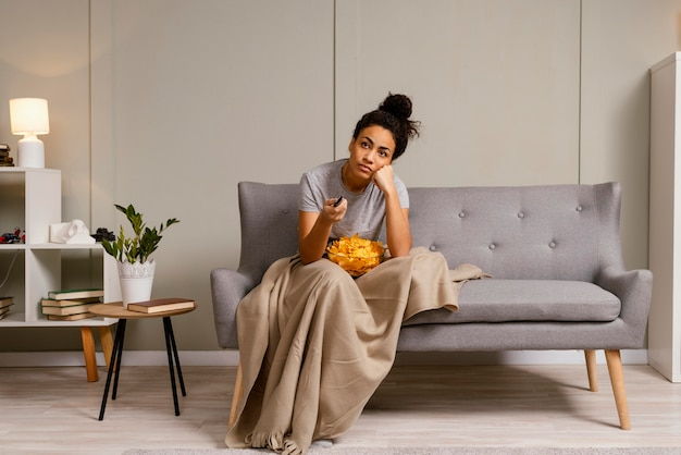 Woman on couch watching tv and eating chips
