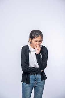A woman coughing and covering her mouth with her hand