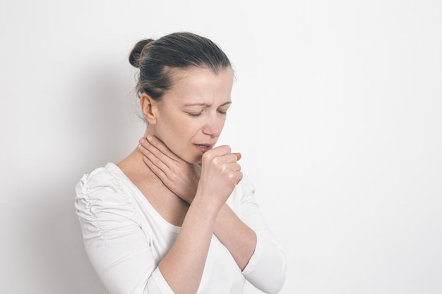 Woman coughing holding on to a sore throat.