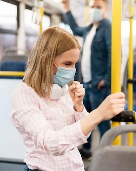 얼굴 마스크와 버스에서 기침하는 여자