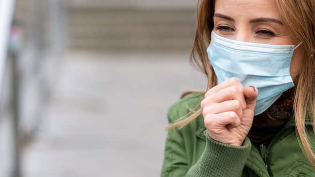 Woman coughing in public space but wearing a mask
