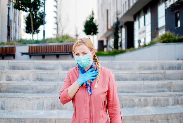 Женщина кашляет, надев защитную медицинскую маску на улице, имея симптом covid-19. молодая женщина с защитной защитной одеждой в городе во время коронавируса