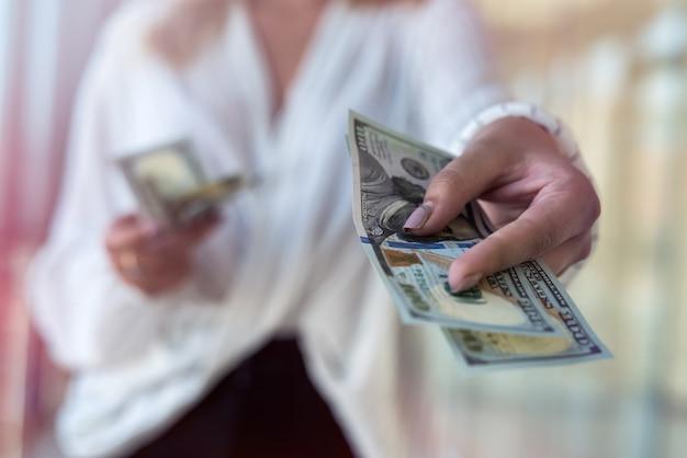 여자는 성공적인 구매 후 쇼핑몰에서 달러를 세다