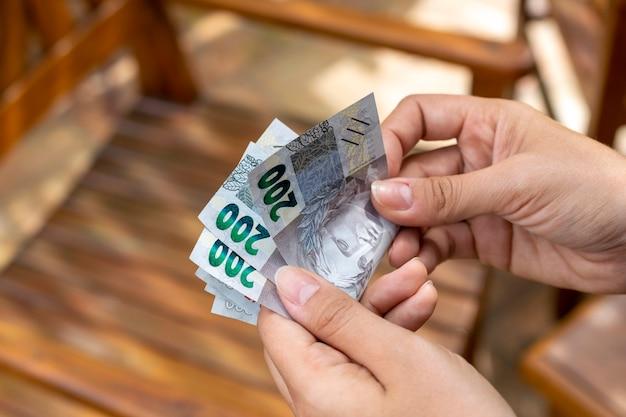 ブラジルのお金の請求書の支払いの概念を数える女性最低賃金の増加
