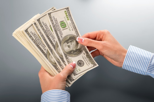 Женщина, считая кучу долларов. женские руки, считающие доллары. приступим к подсчету. интересно, солгали ли они.