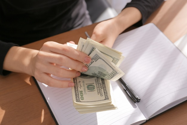 テーブルでドル紙幣を数える女性