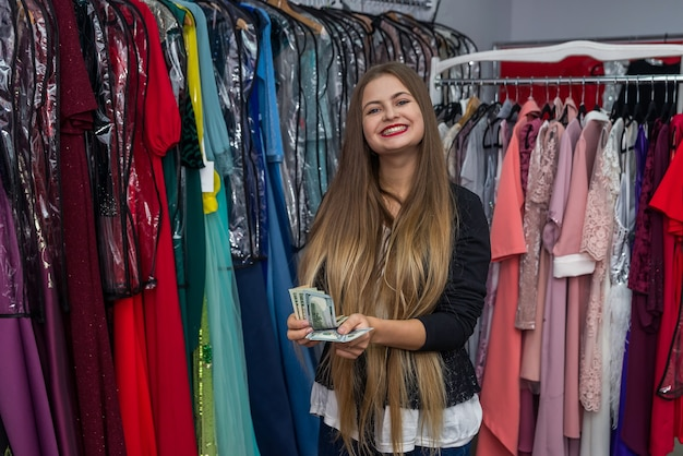 Женщина, считающая долларовые банкноты в магазине платьев