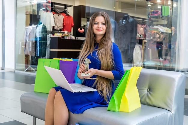 노트북으로 온라인 쇼핑에 대 한 달러를 계산하는 여자