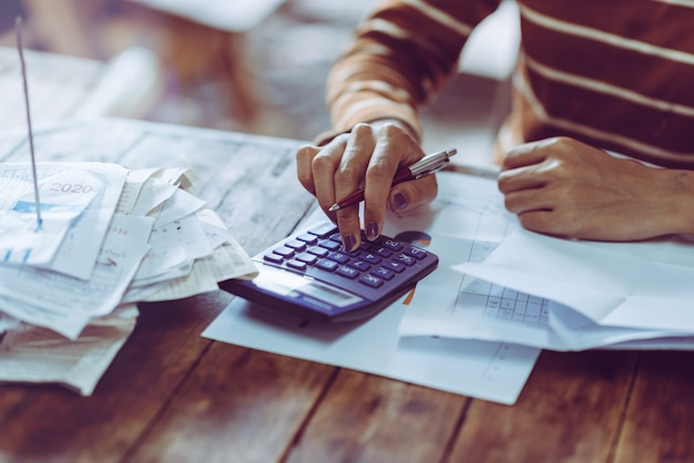 Woman counting finances salary, using calculator, people pressing.