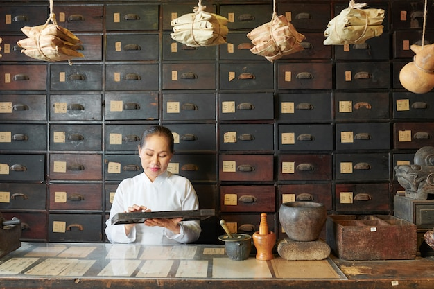 Woman counting ingredients in apothecary