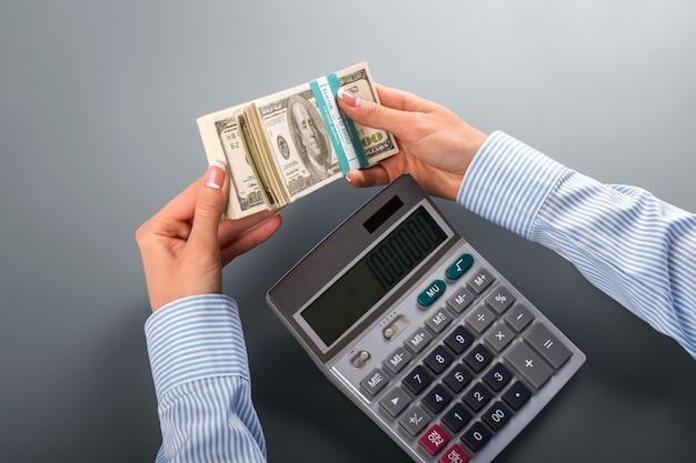 계산기로 돈을 세는 여자. 여성은 계산기 근처에 현금을 보유하고 있습니다. 우리는 부자가 될 것입니다. 이 보기는 매혹적입니다.