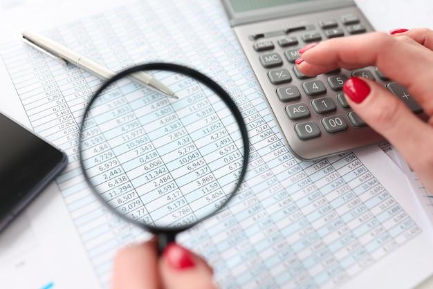 Женщина, рассчитывающая на калькулятор и держащая увеличительное стекло над документом