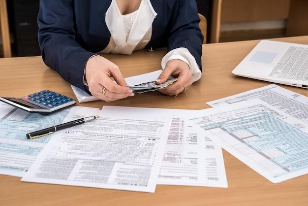 Женщина считает деньги, заполняя налоговые формы