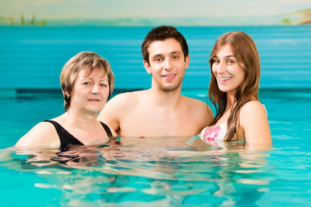 Woman and couple in swimming pool