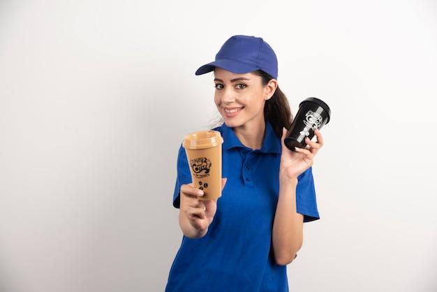 Женщина-курьер дает чашку кофе. фото высокого качества