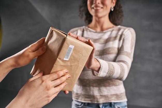 紙のエコバッグでクライアントに小包を与える女性の宅配便