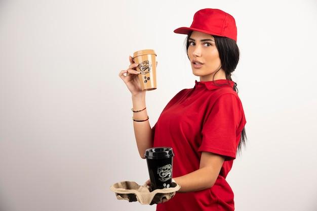 Женщина-курьер плотно держит две чашки кофе. фото высокого качества