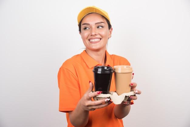 Женщина-курьер держит две чашки кофе смеется.